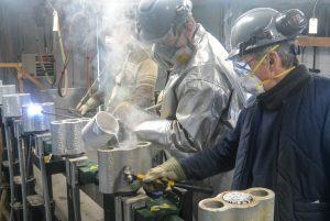 Dès que le métal coule dans le culot, un ouvrier donne de petits coups de marteau pour enlever les bulles d'air. (Photo: Jean-Luc Doumont)