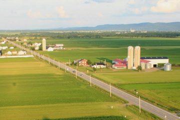 En avant plan, la ferme de Frédéric Savard qui investit dans l'automatisation de sa ferme laitière. Il en profite également pour améliorer le confort de ses vaches. (Photo : courtoisie)